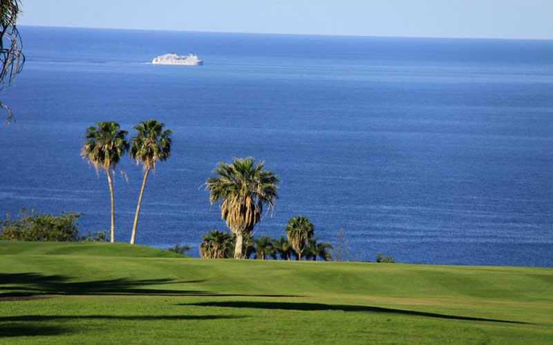 a cruise ship sails past the costa adeje golf course