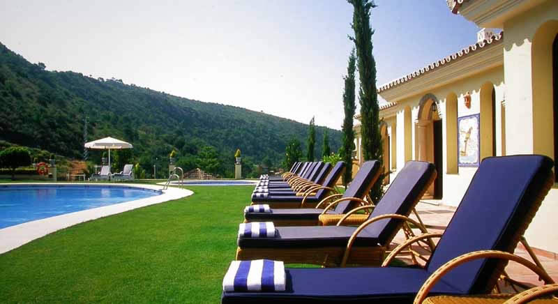 sun beds by the outdoor swimming pool at the gran hotel benahavis