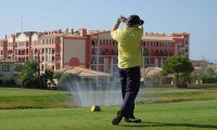 a golfer teeing off with the Bonalba Hotel in the background