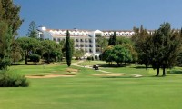 golfers drive their buggies towards the penina golf resort hotel